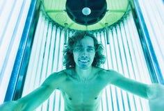 Молодой тонкий человек на солярии в салоне красоты Стоковые Изображения