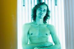 Молодой тонкий человек на солярии в салоне красоты Стоковое Изображение
