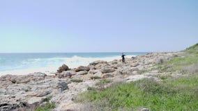 Молодой тонкий sportive человек бежит скалистый след Сильные волны ударяя океан видеоматериал