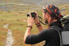 Молодой туристский парень небритый, в шляпе и с безделушками на его руках и рюкзаком на его плечах делает фото стоковые фотографии rf