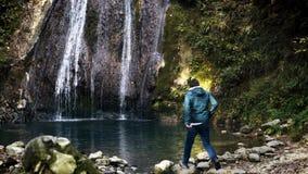 Молодой турист восхищая красивый водопад сток-видео