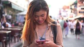 Молодой турист используя мобильный телефон в уличном рынке сток-видео