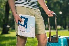 Молодой турист при чемодан держа карту, пасспорты, билеты и кредитную карточку в парке стоковая фотография