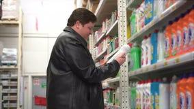 Молодой тучный человек выбирает химикаты домочадца в супермаркете акции видеоматериалы