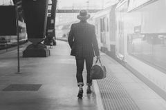 Молодой уверенно испанский бизнесмен при сумка перемещения нося вскользь одежды и шляпу смотря поезд на железной дороге Стоковая Фотография