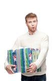 Молодой удивленный человек держа большой тяжелый подарок Стоковые Фотографии RF