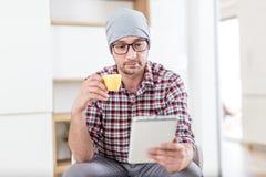 Молодой ультрамодный человек сидя на офисе и наслаждаясь его кофе утр стоковые фото