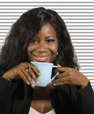 Молодой усмехаться кофе красивой и успешной черной афро американской коммерсантки выпивая уверенный и расслабленный на шторках оф стоковые изображения