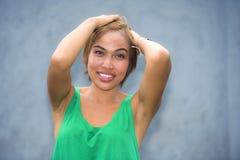 Молодой усмехаться красивой и счастливой азиатской женщины сингапурца или Malay радостный с руками на ее волосах изолированных на Стоковые Изображения RF
