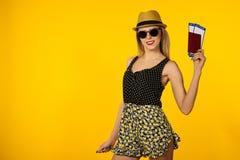 Молодой усмехаясь возбужденный билет посадочного талона паспорта удерживания студента женщины изолированный на желтой предпосылке стоковое изображение rf