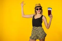 Молодой усмехаясь возбужденный билет посадочного талона паспорта удерживания студента женщины изолированный на желтой предпосылке стоковое изображение
