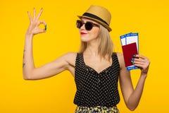 Молодой усмехаясь возбужденный билет посадочного талона паспорта удерживания студента женщины изолированный на желтой предпосылке стоковые изображения rf