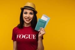 Молодой усмехаясь возбужденный билет посадочного талона паспорта удерживания студента женщины на желтой предпосылке стоковое фото rf