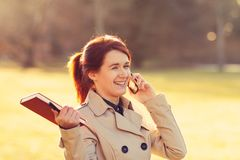 Молодой усмехаясь профессионал студента outdoors держа Красную книгу и говоря на телефоне стоковые фото