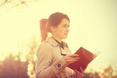 Молодой усмехаясь профессионал студента outdoors держа Красную книгу стоковые изображения