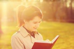 Молодой усмехаясь профессионал студента outdoors держа Красную книгу стоковое фото rf