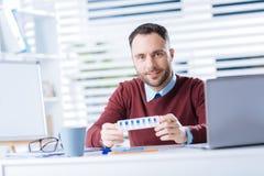 Молодой усмехаясь человек держа коробочку для таблеток пока находящся на работе Стоковые Изображения RF