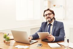 Молодой усмехаясь человек используя компьтер-книжку в современном офисе Стоковые Изображения