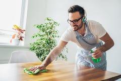 Молодой усмехаясь человек очищая таблицу с ветошью Стоковое фото RF