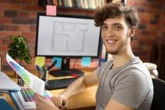 Молодой усмехаясь человек работая на его рабочем месте стоковые изображения