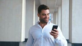 Молодой успешный бизнесмен используя смартфон около офисного здания Рубашка бородатого красивого человека нося белая r акции видеоматериалы