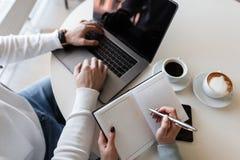 Молодой успешный бизнесмен с ноутбуком и беседы о творческом проекте к девушке коллеги Женщина принимает примечания стоковое изображение