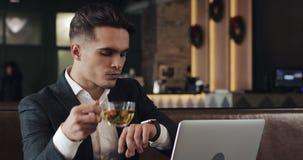 Молодой успешный бизнесмен с smartwatch сидя в кафе Взгляд фрилансера сообщения, активирует применения сток-видео
