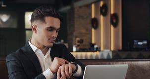 Молодой успешный бизнесмен с smartwatch сидя в кафе Взгляд фрилансера сообщения, активирует применения видеоматериал