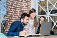 Молодой успешный деловой партнер используя портативный компьютер и сотовый телефон стоковая фотография