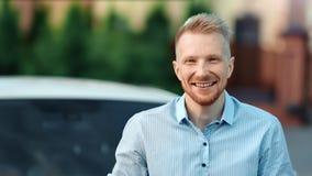 Молодой успешный мужской представлять бизнесмена на открытом воздухе на предпосылке автомобиля смотря камеру акции видеоматериалы