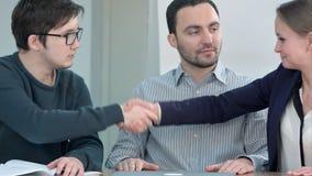 Молодой успешный мужчина и женские партнеры приветствовать, формируя группу для сотруднической работы на проекте, тряся руки Стоковая Фотография RF