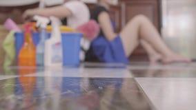 Молодой уставшие человек и женщина сидя на поле спина к спине на предпосылке Очищая день Очищая оборудование сток-видео