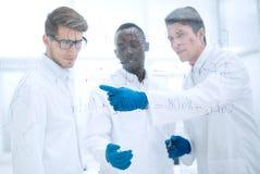 Молодой ученый показывает палец на стеклянной доске стоковое изображение