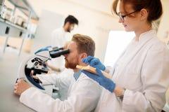 Молодой ученый смотря через микроскоп в лаборатории Стоковое Изображение