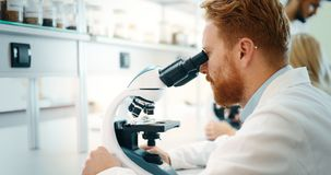 Молодой ученый смотря через микроскоп в лаборатории Стоковая Фотография RF