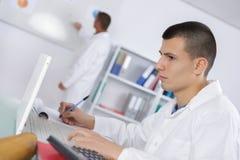 Молодой ученый читает интересное издание исследования стоковое изображение rf