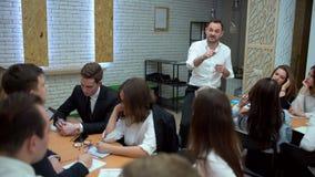 Молодой учитель в классе стоящая склонность его локти на таблице и иметь обсуждать с студентами Человек сток-видео