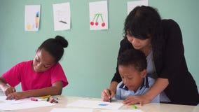 Молодой учитель давая Афро-американским детям урок искусства и уча как нарисовать сток-видео