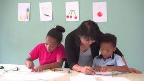 Молодой учитель давая Афро-американским детям урок искусства и уча как нарисовать видеоматериал