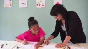 Молодой учитель давая Афро-американскому ребенк урок искусства и уча как нарисовать акции видеоматериалы