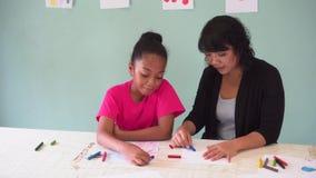 Молодой учитель давая Афро-американскому ребенк урок искусства и уча как нарисовать сток-видео