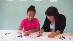 Молодой учитель давая Афро-американскому ребенк урок искусства и уча как нарисовать видеоматериал