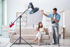 Молодой фотограф работая в студии фото Стоковые Изображения RF