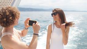 Молодой фотограф фотографируя его подруга на шлюпке моря сток-видео