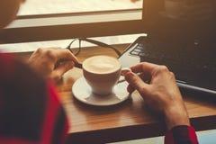 Молодой фрилансер наслаждается кофе в кафе используя компьтер-книжку помадка чашки круасанта кофе пролома предпосылки Работающий  Стоковая Фотография RF
