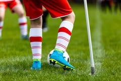 Молодой футболист пиная шарик на футбольном поле Футболист пиная шарик на угле тангажа футбола Стоковое фото RF