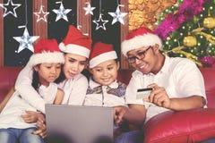 Молодой ходить по магазинам семьи онлайн на времени рождества Стоковая Фотография RF