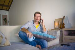 Молодой холодный привлекательный и счастливый человек сидя на сети кресла софы живущей комнаты ослабил говорить имеющ переговор н стоковая фотография rf