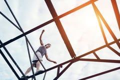 Молодой храбрый человек балансируя на верхней части моста высокого металла Стоковая Фотография