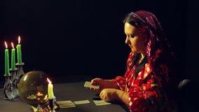 Молодой цыган в удач-говоря салоне светом горящей свечи кладет вне карты для divination на таблицу акции видеоматериалы